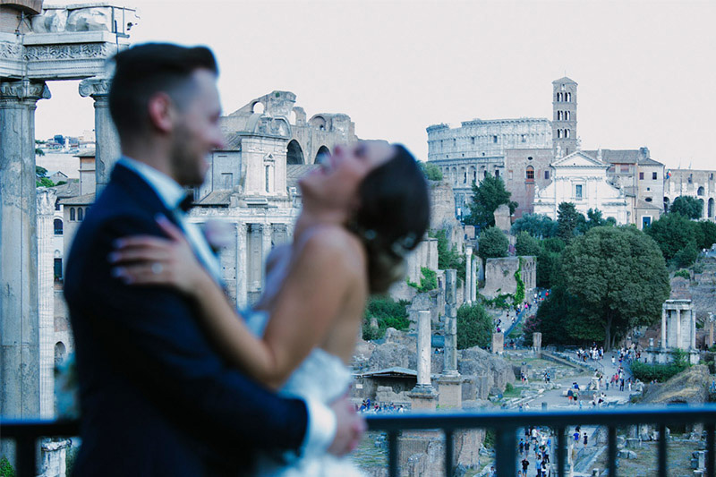 Married couple laughing in photo on balcony overlooking Rome