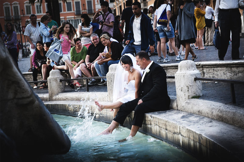 Couple getting their feet wet on the streets of Rome