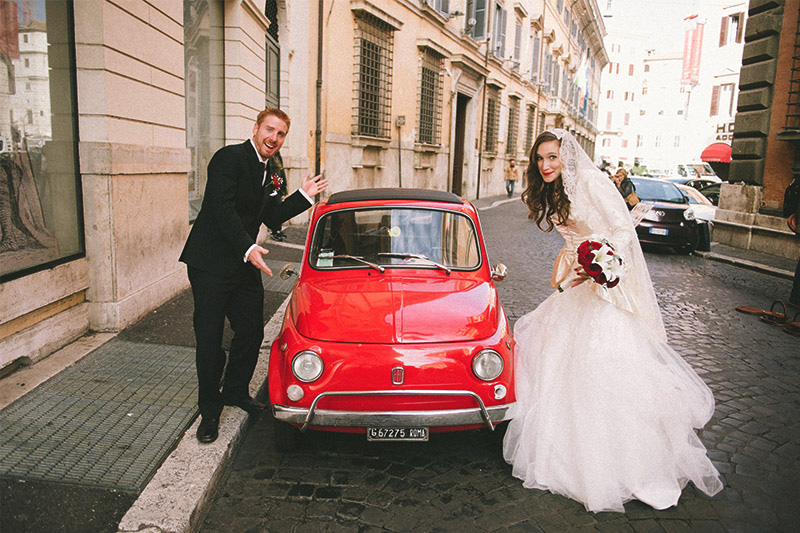 Newly married couple posing with a red car